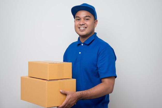 Młody uśmiechnięty azjatycki człowiek dostawy w niebieskim mundurze, trzymając paczkę