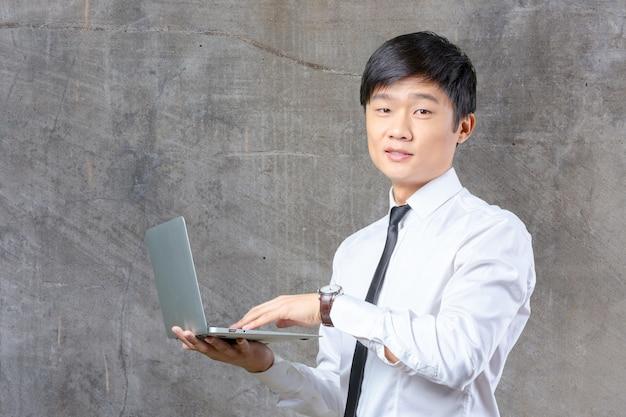 Młody uśmiechnięty azjatykci biznesmena mienia laptop
