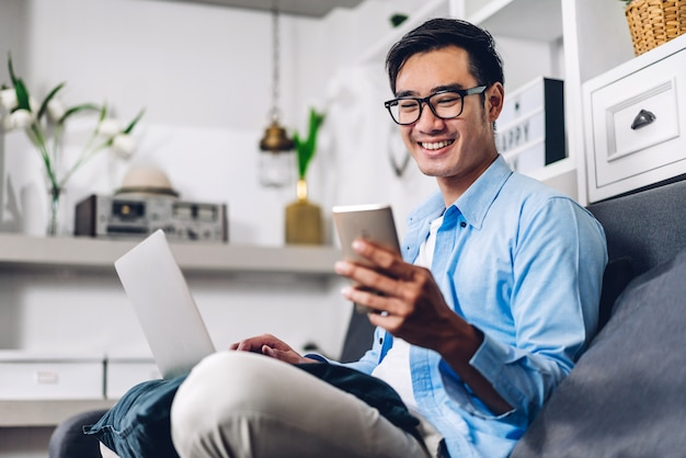 Młody uśmiechnięty azjatykci mężczyzna relaksuje używać laptopu działanie i wideokonferencja spotyka w domu. młody kreatywnie mężczyzna patrzeje ekranową pisać na maszynie wiadomość z smartphone. praca z domu koncepcji