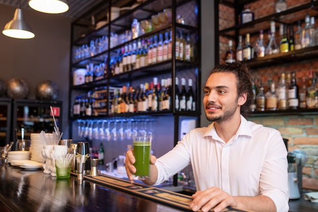 Młody uśmiechnięty barman trzyma szklankę zielonego koktajlu lub smoothie wynagrodzenia na ladzie, obsługując jednego z klientów w kawiarni lub restauracji