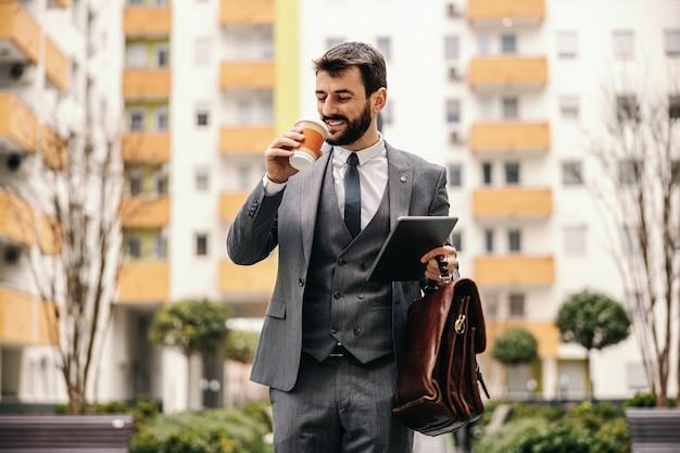 Młody uśmiechnięty biznesmen modne picia kawy i idzie do pracy.