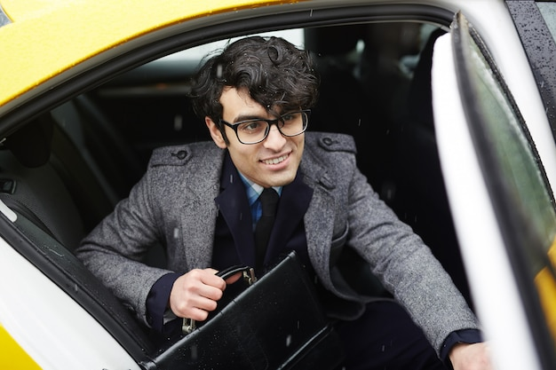 Młody uśmiechnięty biznesmen opuszcza taxi w deszczu
