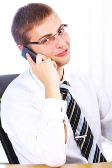 Młody uśmiechnięty biznesmen używa telefon komórkowego