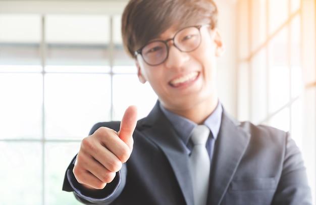 Młody uśmiechnięty biznesmen z szkłami pokazuje aprobaty. koncepcja sukcesu firmy