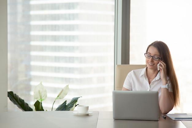 Młody uśmiechnięty bizneswoman opowiada na telefonie przy miejscem pracy, komunikacja mobilna