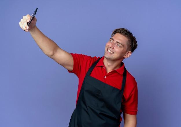 Młody uśmiechnięty blond mężczyzna fryzjer w mundurze patrzy na telefon, biorąc selfie na białym tle na fioletowej przestrzeni z miejsca na kopię