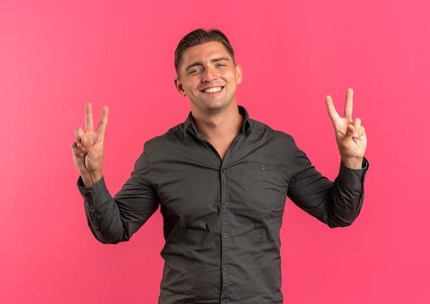 Młody uśmiechnięty blondynka przystojny mężczyzna gesty ręką znak zwycięstwa