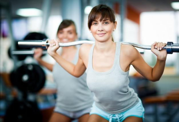 Młody uśmiechnięty brunetki kobiety instruktor w szarym sportswear pokazuje jak robić sztangi kucać
