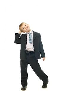 Młody uśmiechnięty chłopiec w stroju na białym młody chłopak biznesmen