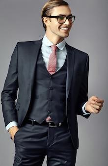 Młody uśmiechnięty elegancki przystojny biznesmen model mężczyzna w garniturze i modne okulary