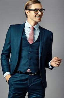 Młody uśmiechnięty elegancki przystojny biznesmen samiec model w kostiumu i modnych szkłach pozuje w studiu