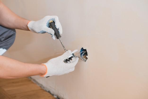 Młody uśmiechnięty elektryk instaluje elektrycznego gniazdko na ścianie w domu