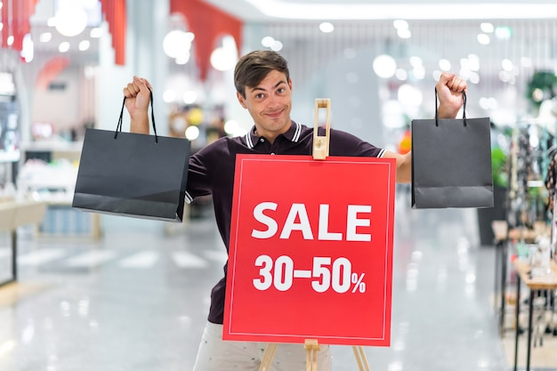 Młody uśmiechnięty facet pozuje w bordowej koszulce i beżowych szortach trzymając kolorowe torby. pozowanie na tle banera z napisem wyprzedaż i rabaty do 30-50 proc