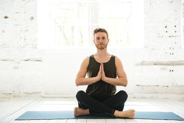 Młody uśmiechnięty facet siedzi na fitness matę i medytacji