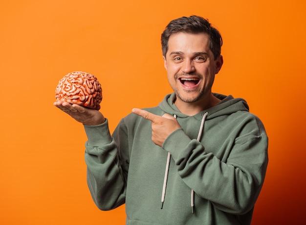 Młody uśmiechnięty facet z mózgiem na pomarańczowo