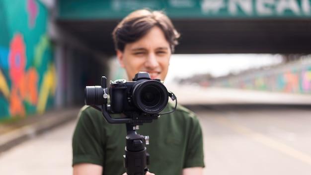 Młody uśmiechnięty fotograf z aparatem na statywie podczas sesji zdjęciowej na drodze