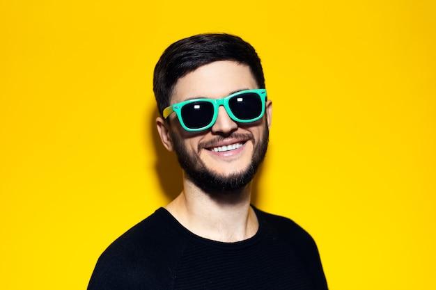Młody uśmiechnięty hipster z aqua menthe okulary na pomarańczowej ścianie.