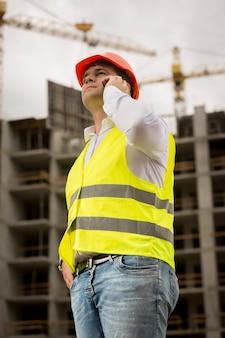 Młody uśmiechnięty inżynier rozmawia przez telefon przy budynku w budowie