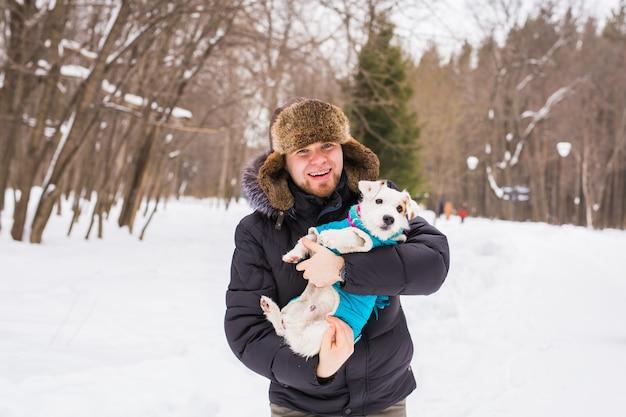 Młody uśmiechnięty kaukaski mężczyzna trzyma jack russell terrier na zewnątrz w okresie zimowym