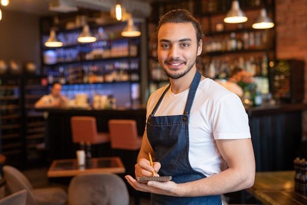 Młody uśmiechnięty kelner w odzieży roboczej robiąc notatki w notatniku, stojąc przed kamerą na tle baru i wnętrza