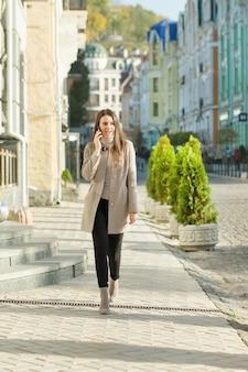 Młody uśmiechnięty kobiety odprowadzenie na miasto ulicie, jesień słoneczny dzień