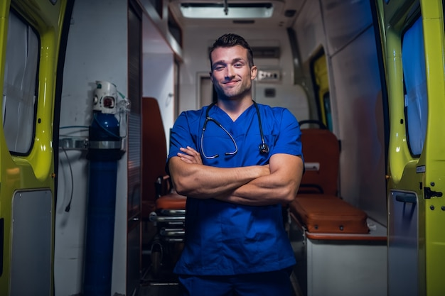 Młody uśmiechnięty lekarz w niebieskim mundurze stojąc i patrząc w kamerę.