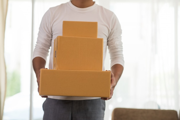 Młody uśmiechnięty logistycznie doręczeniowy mężczyzna trzyma pudełko