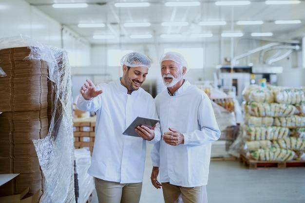 Młody uśmiechnięty menedżer w sterylnym mundurze za pomocą tabletu do sprawdzania towarów i rozmowy z pracownikiem. wnętrze fabryki żywności.
