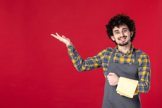 Młody uśmiechnięty męski serwer z kręconymi włosami trzymający ręcznik wskazujący coś po prawej stronie, stojący na odizolowanym czerwonym tle