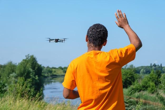 Młody uśmiechnięty mężczyzna afroamerykanów obsługujący drona z kontrolerem stojąc z tyłu i machając ręką na łące w pobliżu rzeki.