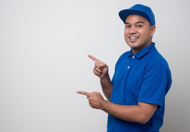 Młody uśmiechnięty mężczyzna azji dostawy w mundurze i wskazując