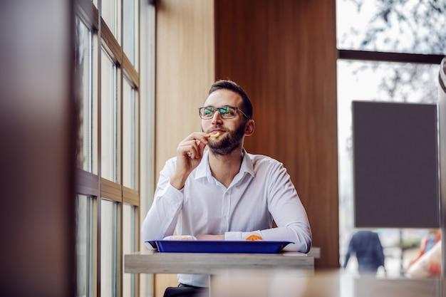 Młody uśmiechnięty mężczyzna elegancko ubrany siedzi w restauracji typu fast food, je frytki i robi sobie przerwę w pracy.