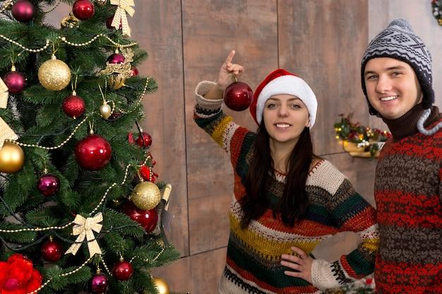 Młody uśmiechnięty mężczyzna i kobieta w śmiesznych czapkach, dekorujący na boże narodzenie, wieszający dekoracje i ozdoby na dużej choince w swoim salonie