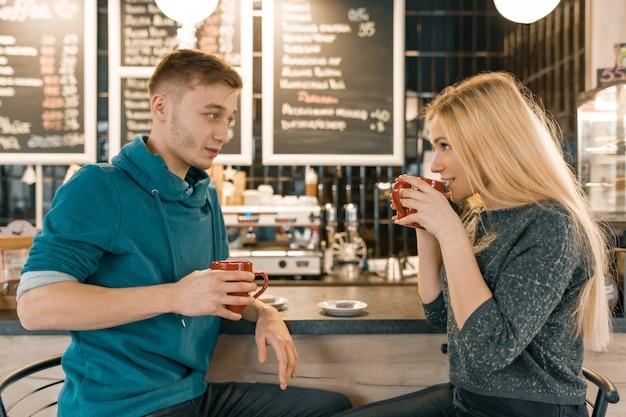 Młody uśmiechnięty mężczyzna i kobieta wpólnie opowiada w sklep z kawą