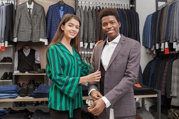 Młody uśmiechnięty mężczyzna i sklepowy konsultant pozuje przy kamerą.