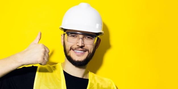 Młody uśmiechnięty mężczyzna, inżynier konstruktora, pokazujący kciuki do góry, ubrany w biały kask ochronny, okulary i żółtą kurtkę na żółtej ścianie z miejscem na kopię.