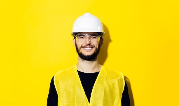 Młody uśmiechnięty mężczyzna, inżynier konstruktora, ubrany w biały kask ochronny, okulary i żółtą kurtkę na białym tle na żółtej ścianie.
