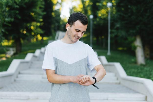 Młody uśmiechnięty mężczyzna konfiguruje jego mądrze zegarek sprawności fizycznej zespół przed ćwiczeniem lub sprawdza to po tym w parku lub na zewnątrz.