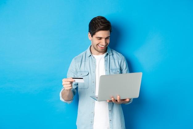 Młody uśmiechnięty mężczyzna kupuje w internecie, trzymając kartę kredytową i płacąc za zakup z laptopem, stojąc nad niebieską ścianą