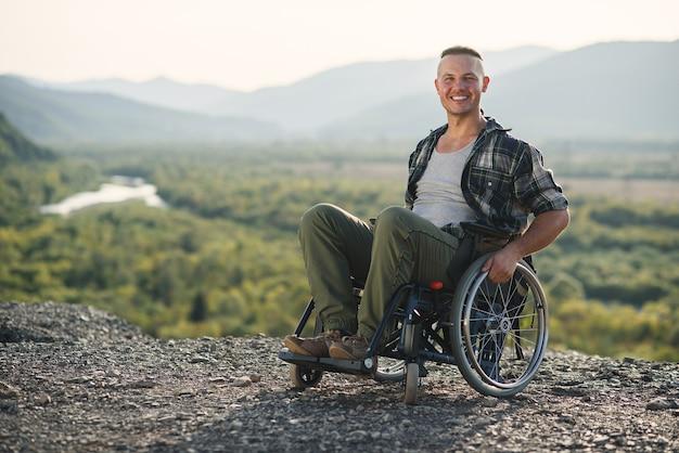 Młody uśmiechnięty mężczyzna na wózku inwalidzkim, ciesząc się pięknem przyrody w górach. podróżowanie osób niepełnosprawnych.