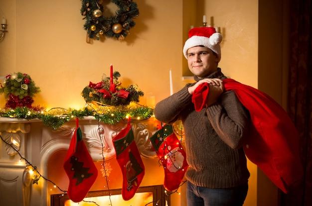 Młody uśmiechnięty mężczyzna niosący dużą torbę świętego mikołaja z prezentami w wigilię bożego narodzenia