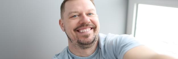 Młody uśmiechnięty mężczyzna robi selfie w domu