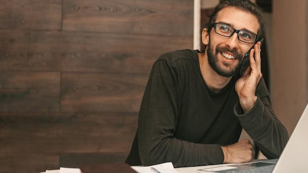 Młody uśmiechnięty mężczyzna rozmawia przez telefon podczas pracy w domu