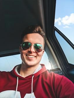 Młody uśmiechnięty mężczyzna siedzi na tylnym siedzeniu taksówki jadącej na lotnisko i robi sobie selfie