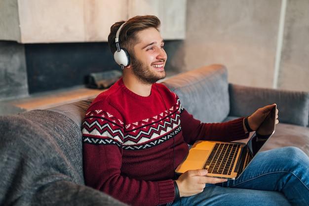 Młody uśmiechnięty mężczyzna siedzi w domu zimą, macha ręką, ma na sobie czerwony sweter, pracuje na laptopie, freelancer, słucha słuchawek, student studiuje online