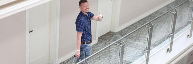 Młody uśmiechnięty mężczyzna stoi w hotelowym korytarzu i pokazuje gest kciuka w górę