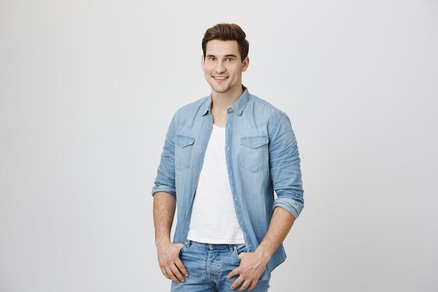 Młody uśmiechnięty mężczyzna stojący na białej ścianie