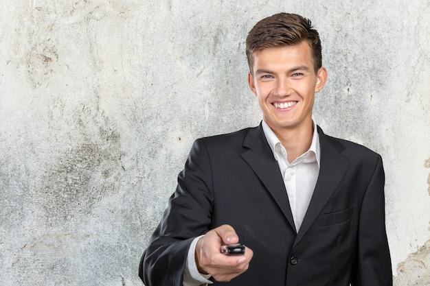Młody uśmiechnięty mężczyzna trzyma kluczyki do samochodu