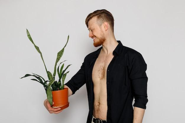 Młody uśmiechnięty mężczyzna trzyma w rękach mały kwiatek na białym tle.
