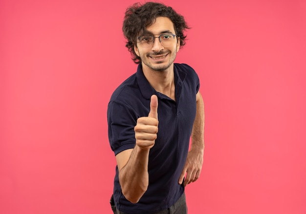Młody uśmiechnięty mężczyzna w czarnej koszuli z okularami optycznymi kciuki do góry i wygląda na białym tle na różowej ścianie